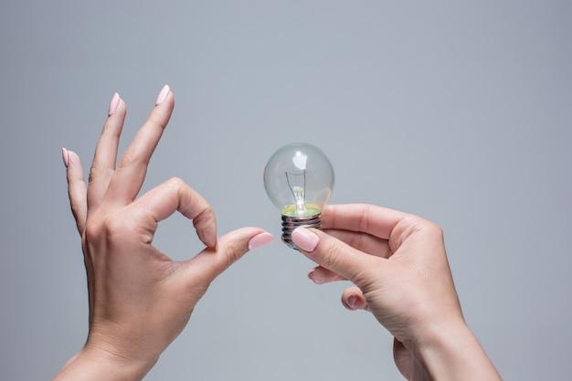 Mão segurando uma lâmpada incandescente em fundo cinza