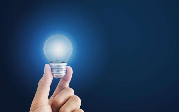 Mão segurando uma lâmpada incandescente, sobre fundo azul