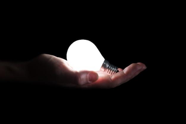 Mão segurando uma lâmpada incandescente