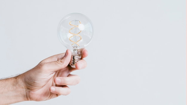 Mão segurando uma lâmpada