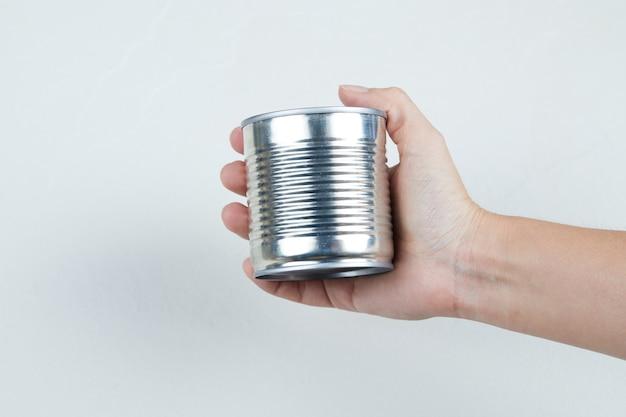 Mão segurando uma lata de milho doce cozido.