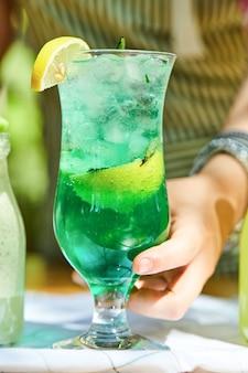 Mão segurando uma limonada na mesa de madeira.