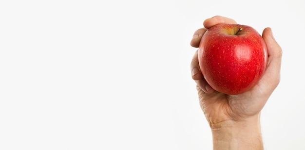 Mão segurando uma maçã com espaço de cópia