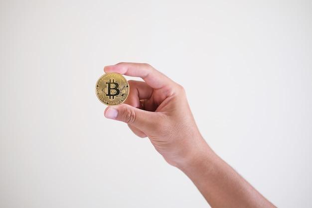Mão segurando uma moeda criptomoeda de ouro isolada no fundo branco