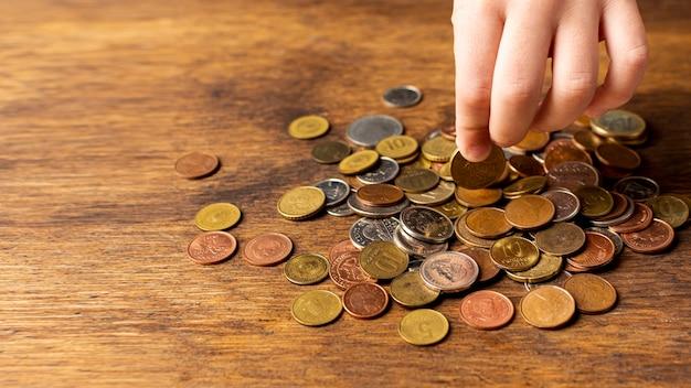 Mão segurando uma moeda de uma pilha