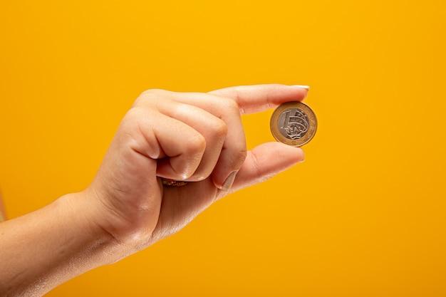Mão segurando uma moeda real do conceito de finanças do brasil.