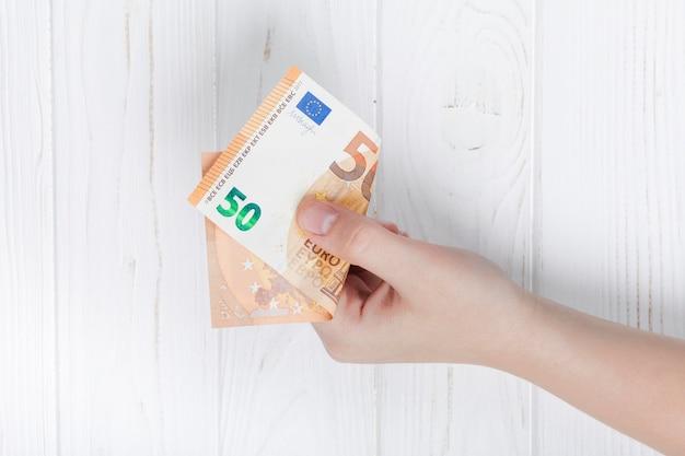 Mão segurando uma nota de banco do euro