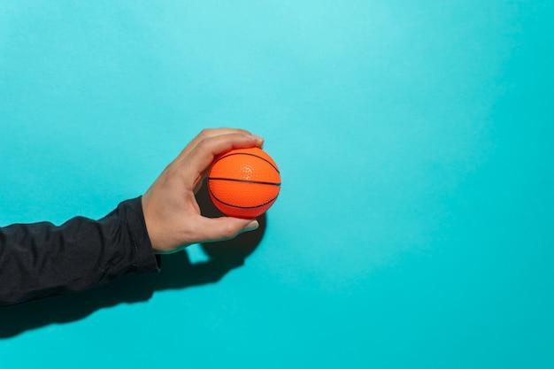 Mão segurando uma pequena bola de basquete na frente de um fundo colorido azul com espaço de cópia para o texto