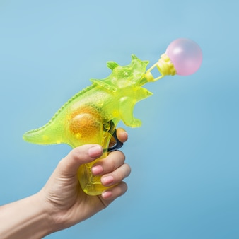Mão segurando uma pistola d'água na forma de um rinoceronte soprando uma bolha
