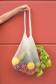 Mão segurando uma sacola com vegetais de perto