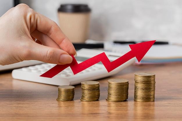Mão segurando uma seta de crescimento com moedas