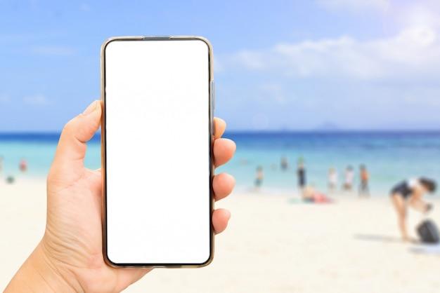 Mão segurando uma tela em branco do telefone na praia