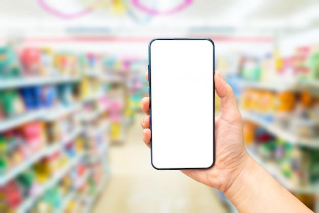 Mão segurando uma tela em branco do telefone no supermercado turva