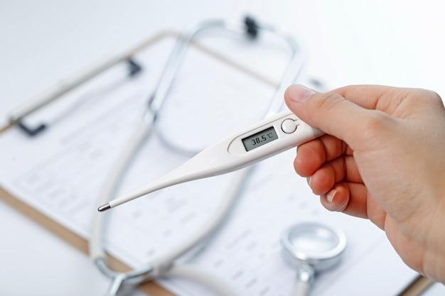 Mão segurando uma temperatura do corpo mesurador