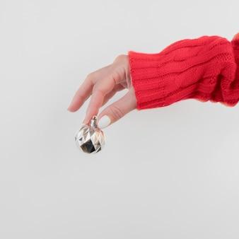 Mão segurando uma vista frontal de bola de natal