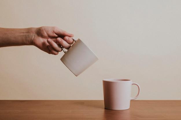 Mão segurando uma xícara de café de cerâmica