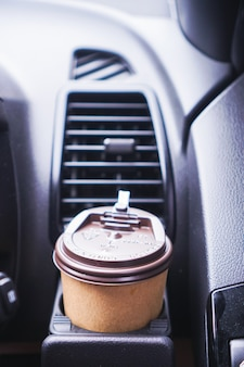 Mão segurando uma xícara de café de papel enquanto dirige um carro pela manhã