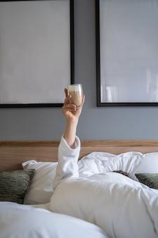 Mão segurando uma xícara de café em casa na cama