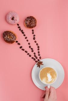 Mão segurando uma xícara de café, feijão e três donuts no fundo rosa