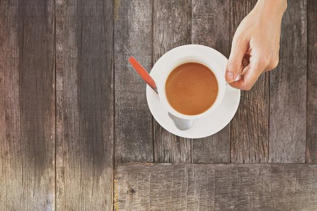 Mão segurando uma xícara de café na mesa de madeira.