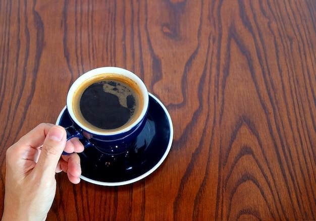 Mão segurando uma xícara de café quente