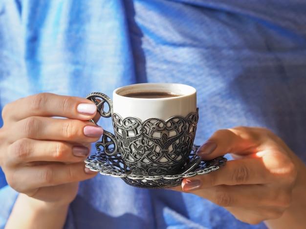 Mão segurando uma xícara de café. uma xícara de café turco, segurando as mãos das mulheres.