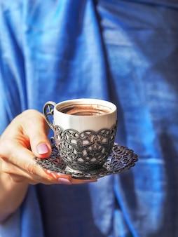 Mão segurando uma xícara de café.