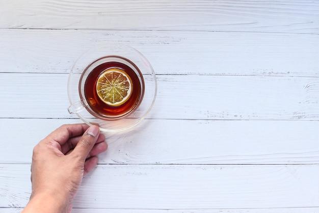 Mão segurando uma xícara de chá de limão com espaço de cópia.