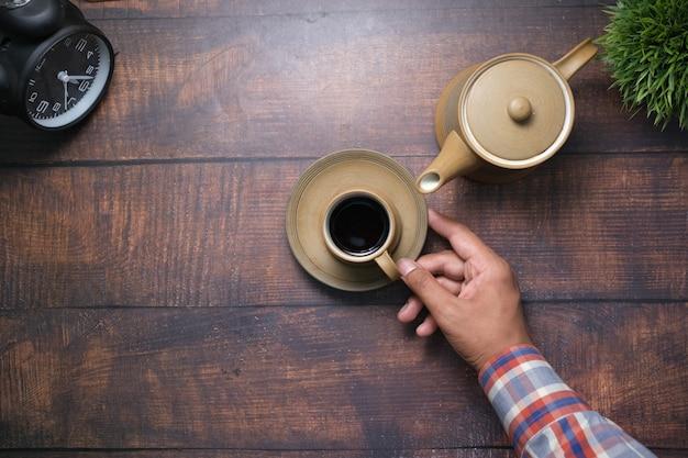 Mão segurando uma xícara de chá verde com espaço de cópia
