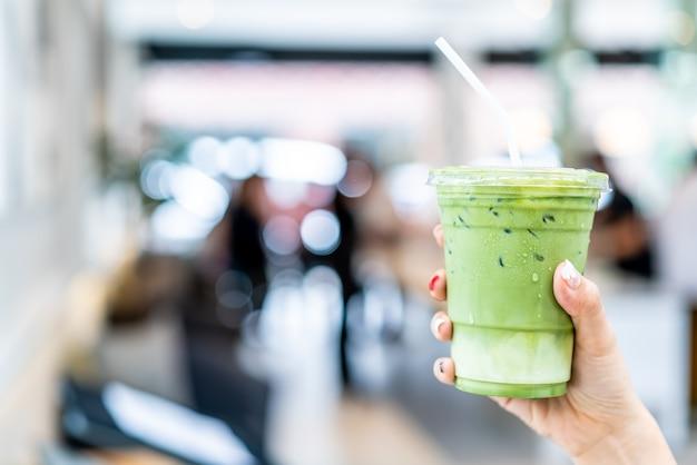 Mão segurando uma xícara de chá verde matcha com leite gelado