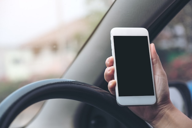 Mão segurando & usando telefone celular branco com tela de desktop em branco preto enquanto estiver dirigindo o carro