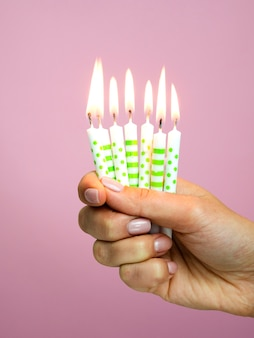 Mão segurando velas de aniversário em fundo rosa