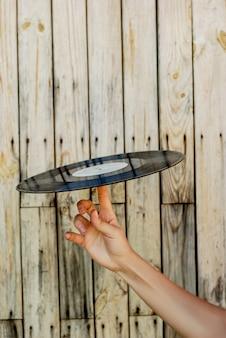 Mão, segurando, vinil, registro, sobre, madeira, fundo
