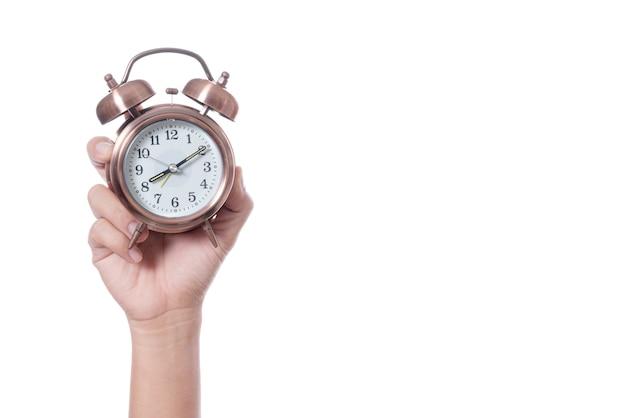 Mão segurando vintage despertador às 07:00 e mostrando o tempo mais de oito horas