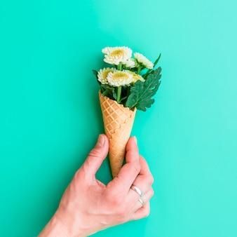 Mão, segurando, waffle, cone, com, flores brancas