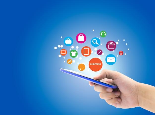 Mão segurar celular, smartphone com conceito online de compras no fundo azul