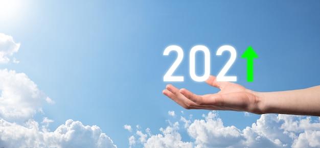 Mão segure 2021 ícone positivo no fundo do céu. plano de negócios positivo crescimento no conceito do ano 2021. plano de empresário e aumento de indicadores positivos em seu negócio, crescendo os conceitos de negócios.
