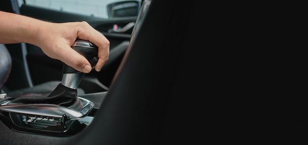 Mão segure a alavanca do carro de transmissão automática. dirigindo o automóvel com engrenagens automáticas e copyspace