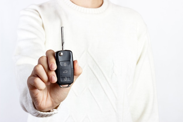 Mão segure a chave do carro em brancos