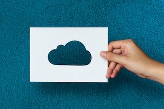 Mão segure a escultura de papel de nuvem com fundo azul