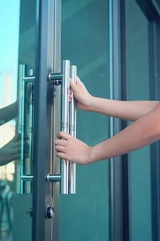 Mão segure a maçaneta da porta para abrir o escritório.