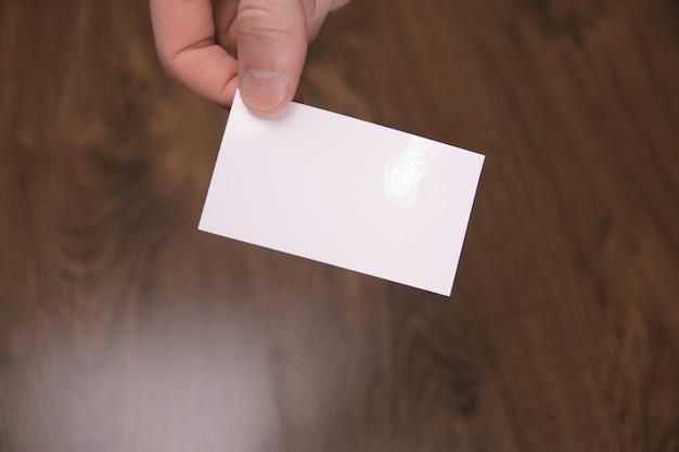 Mão segure a maquete de cartão branco em branco com cantos arredondados. modelo de cartão de chamada simples, segurando o braço. visor de cartão de visita de plástico em plástico. verifique o design do cartão deslocado. identidade visual da empresa.