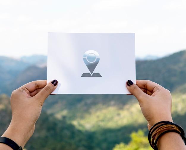Mão segure alfinete etiqueta escultura em papel com fundo de montanha