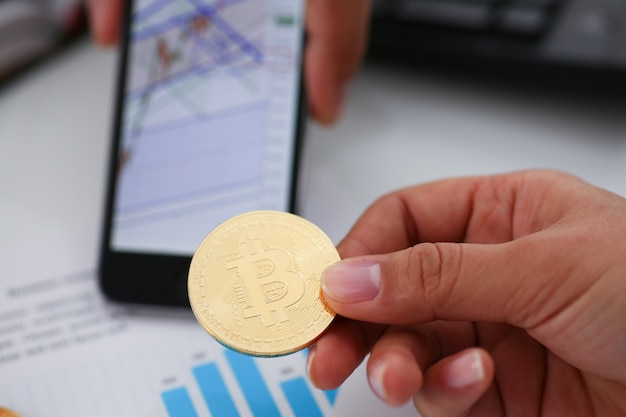 Mão segure bitcoin documentos smartphone closeup