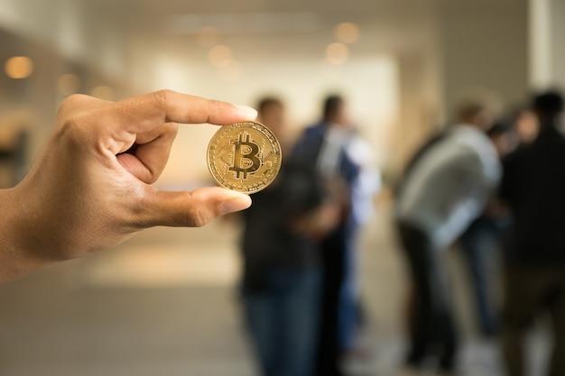 Mão segure bitcoin na frente turva pessoas reunião fundo