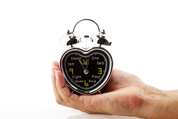 Mão segure coração despertador isolado no espaço de cópia de fundo branco para o seu texto.