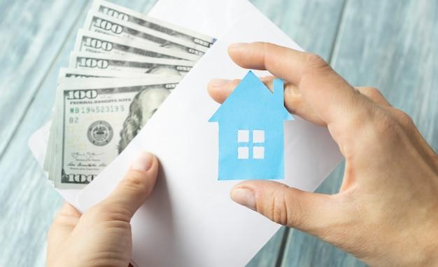 Mão segure envelope com dinheiro em dólares, economia para casa