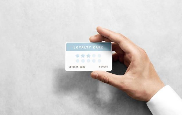 Mão segure maquete de cartão de desconto com cantos arredondados