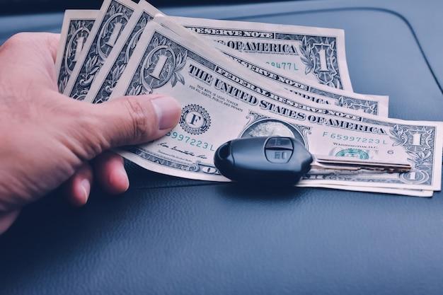 Mão segure notas de dólar com chave do carro