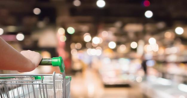 Mão segure o carrinho de compras de supermercado com prateleiras de mercearia